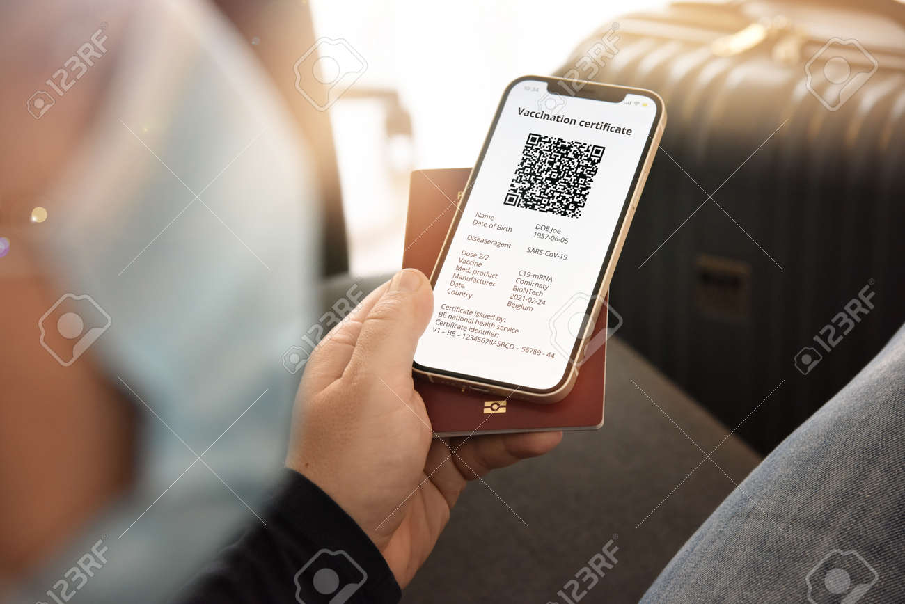 Man with face mask holding smartphone with digital certificate of vaccination against and passport. Travel and tourism concept during pandemic. - 167164224