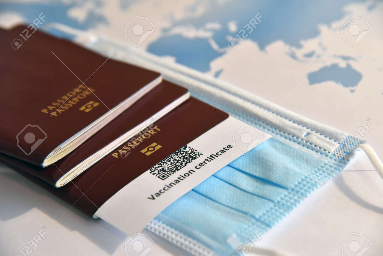 Travel in the era of . Passports, certificate of vaccination against and face mask in front of the world map. - 167164327
