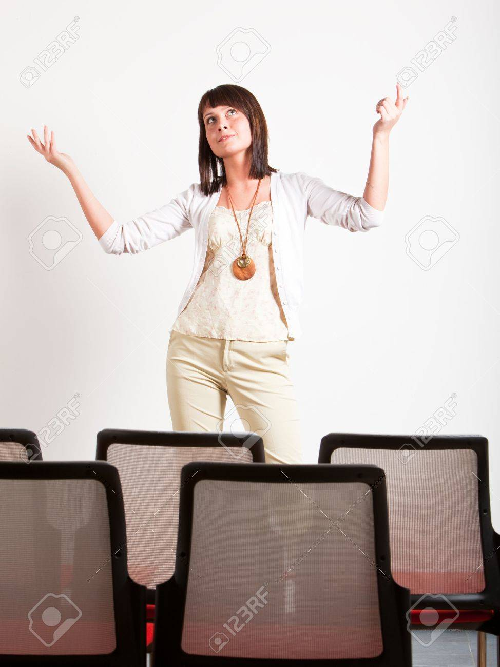 woman making a presentation in class, explaining with hands up Stock Photo - 6489994