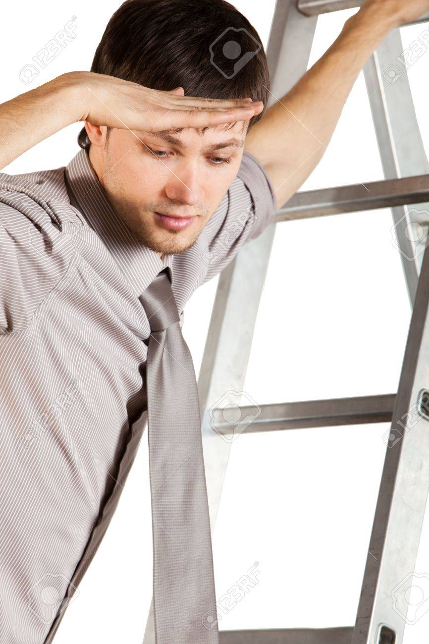 a handsome young businessman rolled up sleeves climbing a handsome young businessman rolled up sleeves climbing up the ladder and lookign down