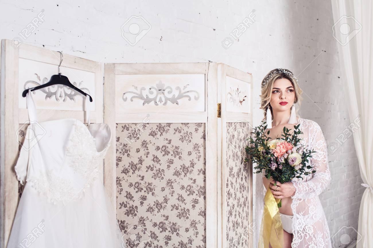 Bride Dressed In Peignoir And Underwear Stands Near Shield