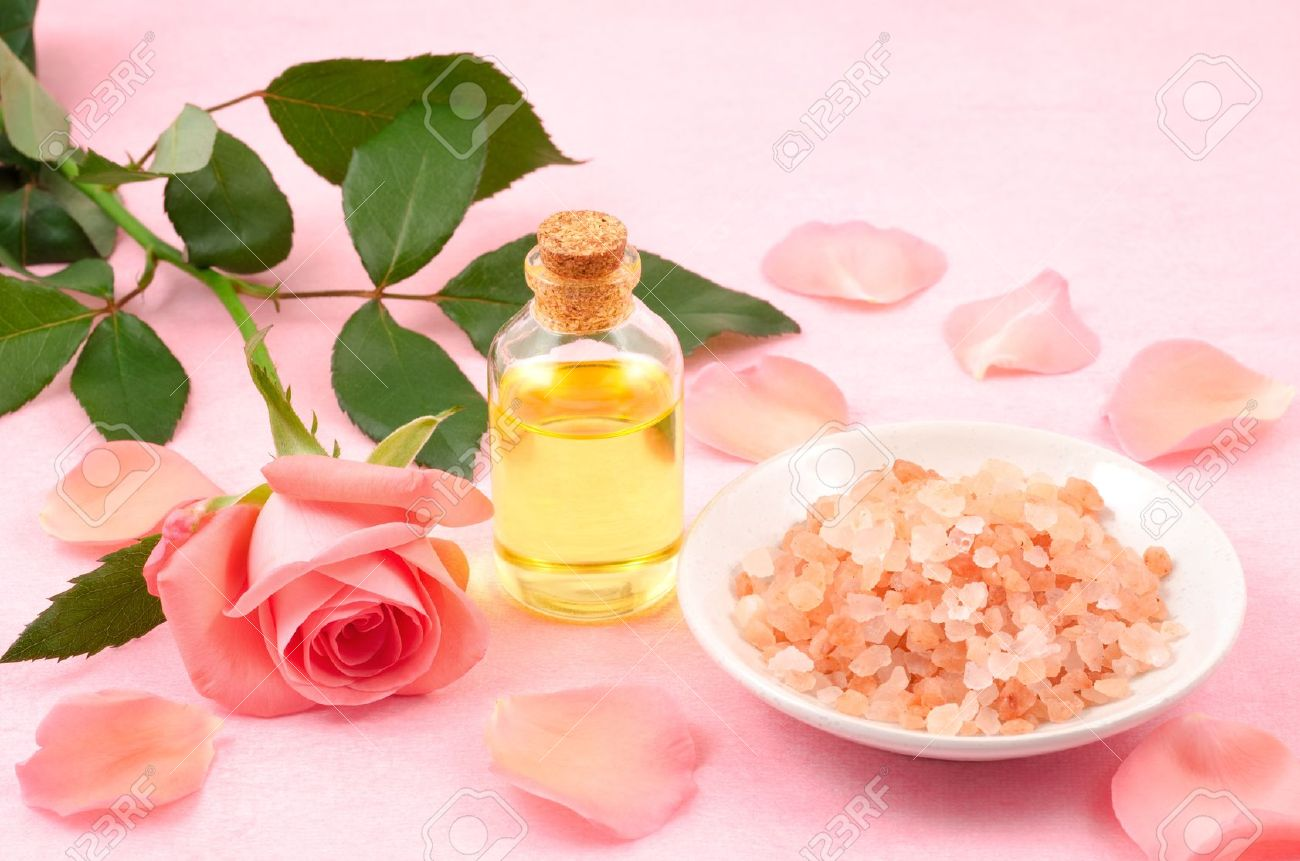 Essential oil and himalayan salt,rose petals on pink background Stock Photo - 16431939