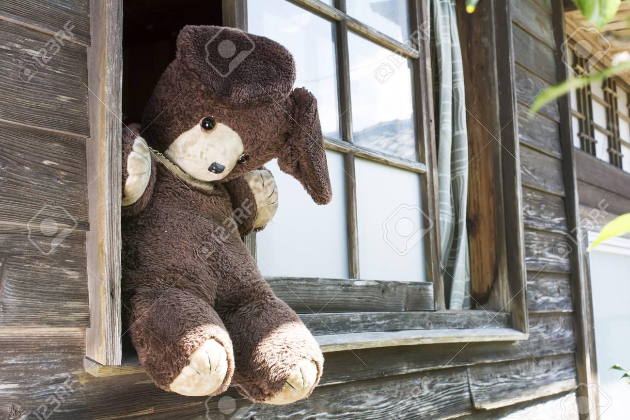 木造の建物の窓の敷居に古いクマのぬいぐるみの斜めビュー