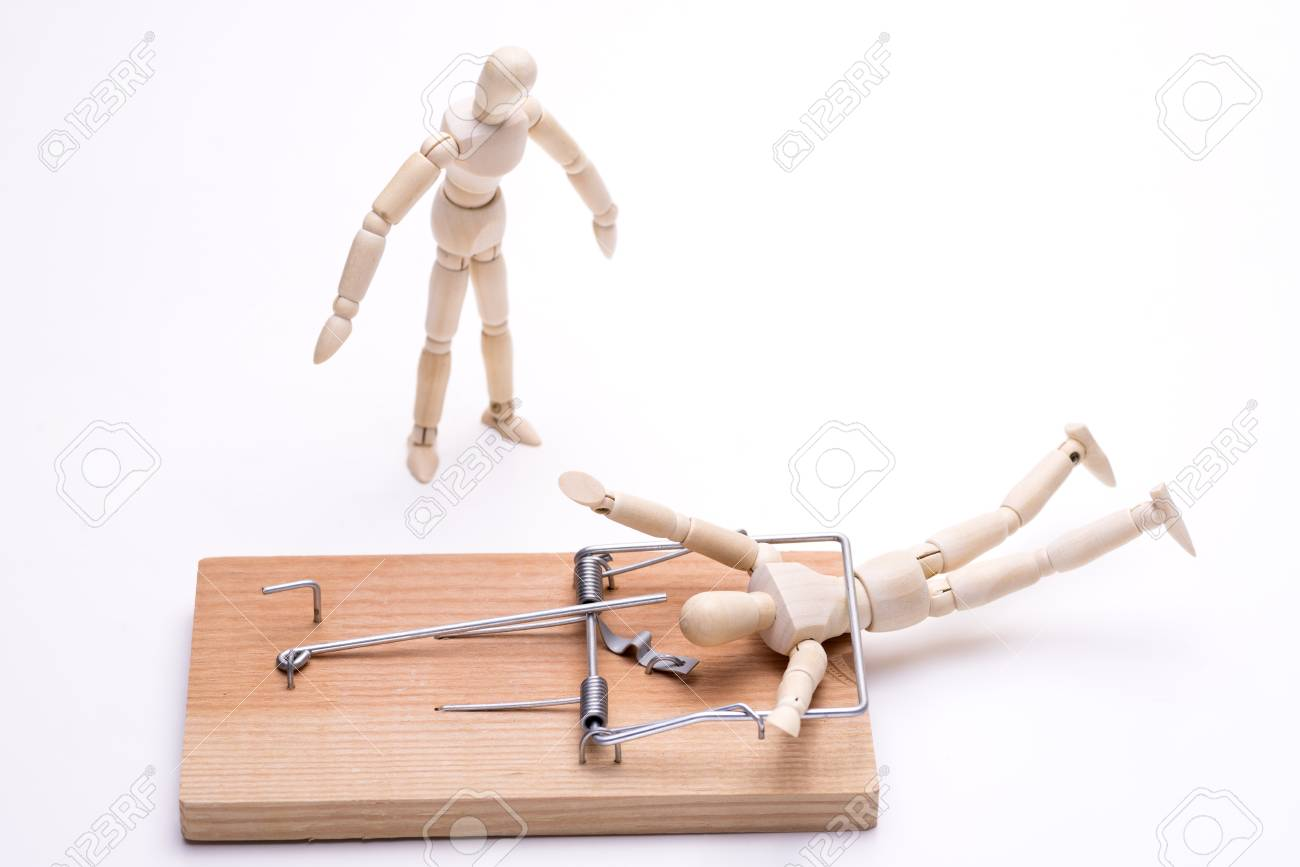 Wooden doll caught in a mouse trap and bystander in front of white background - 112698548