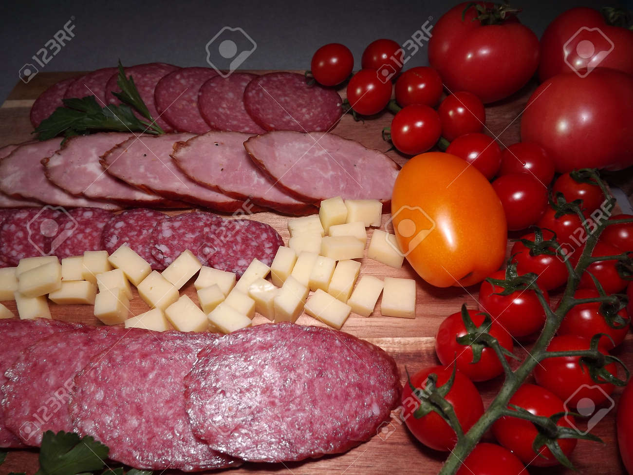 slicing smoked sausage of four varieties with cheese and red and yellow tomatoes and cherry tomatoes. High quality photo - 166249300