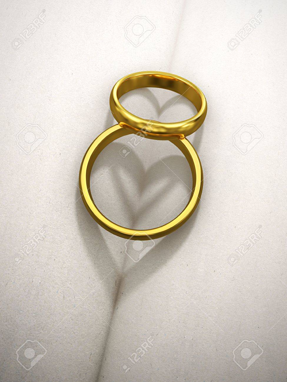 Two Golden Wedding Rings With Heart Shaped Shadow Stock Photo