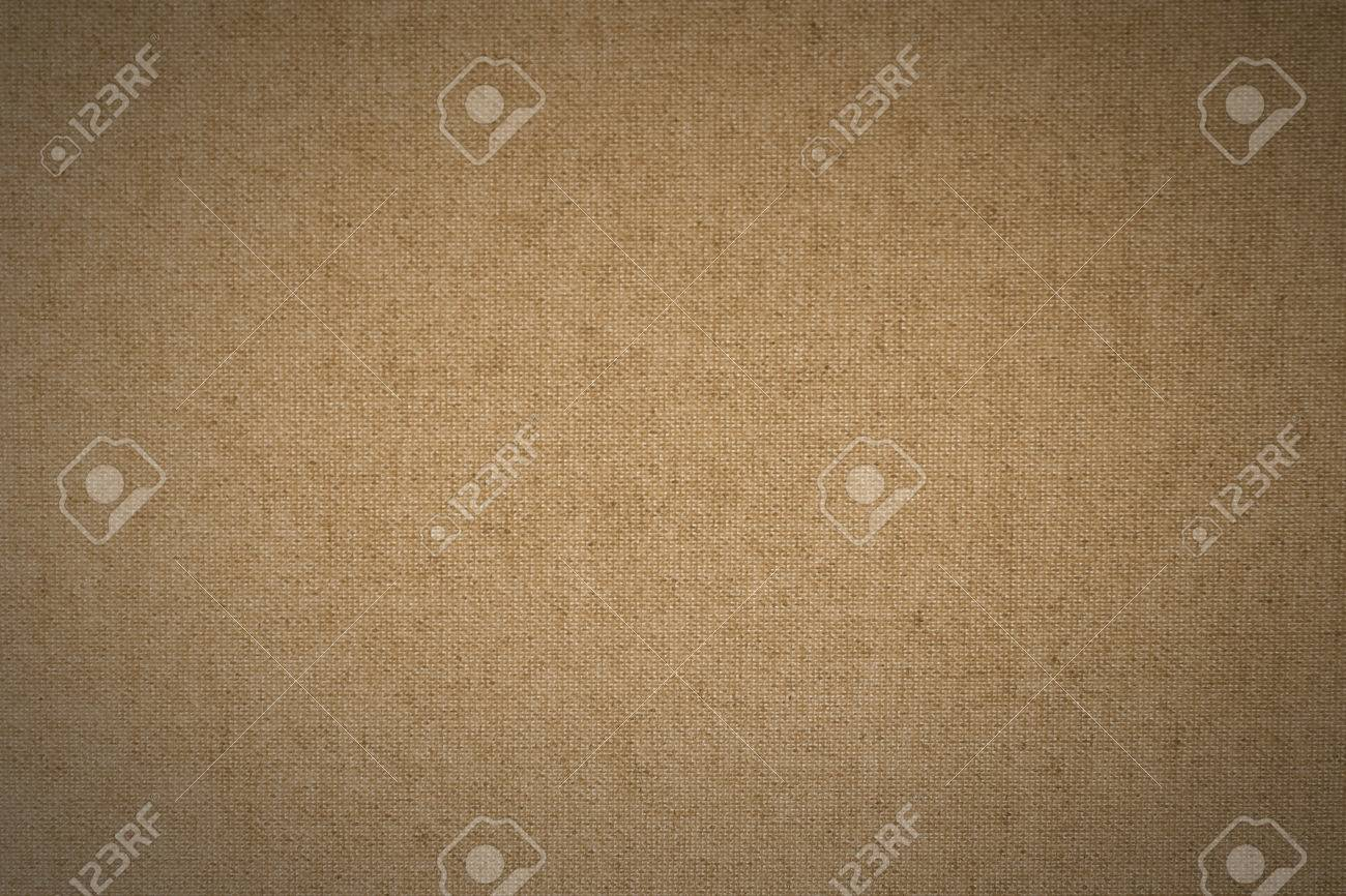 background of light brown linen fabric with characteristic interlacings and fiber structure and small dark areas brown linen fabric lighting
