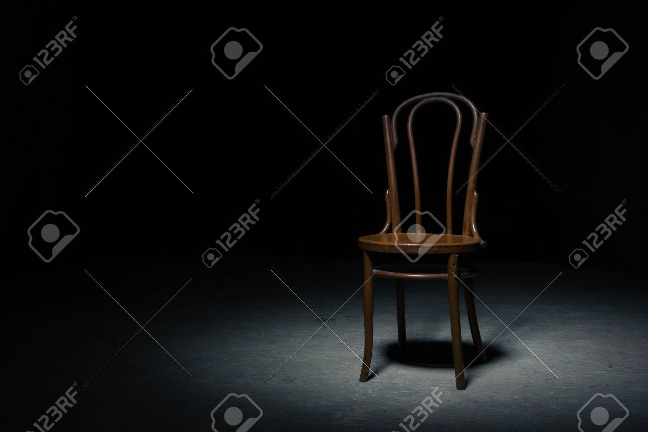 Lonely Chair In The Spot Of Light On Black Background At Empty Room Stock Photo