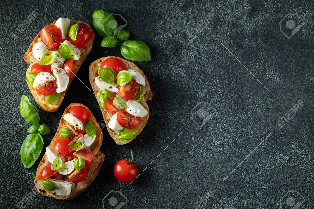 Bruschetta with tomatoes, mozzarella cheese and basil on a dark background. Traditional italian appetizer or snack, antipasto. Top view with copy space. Flat lay - 125681172