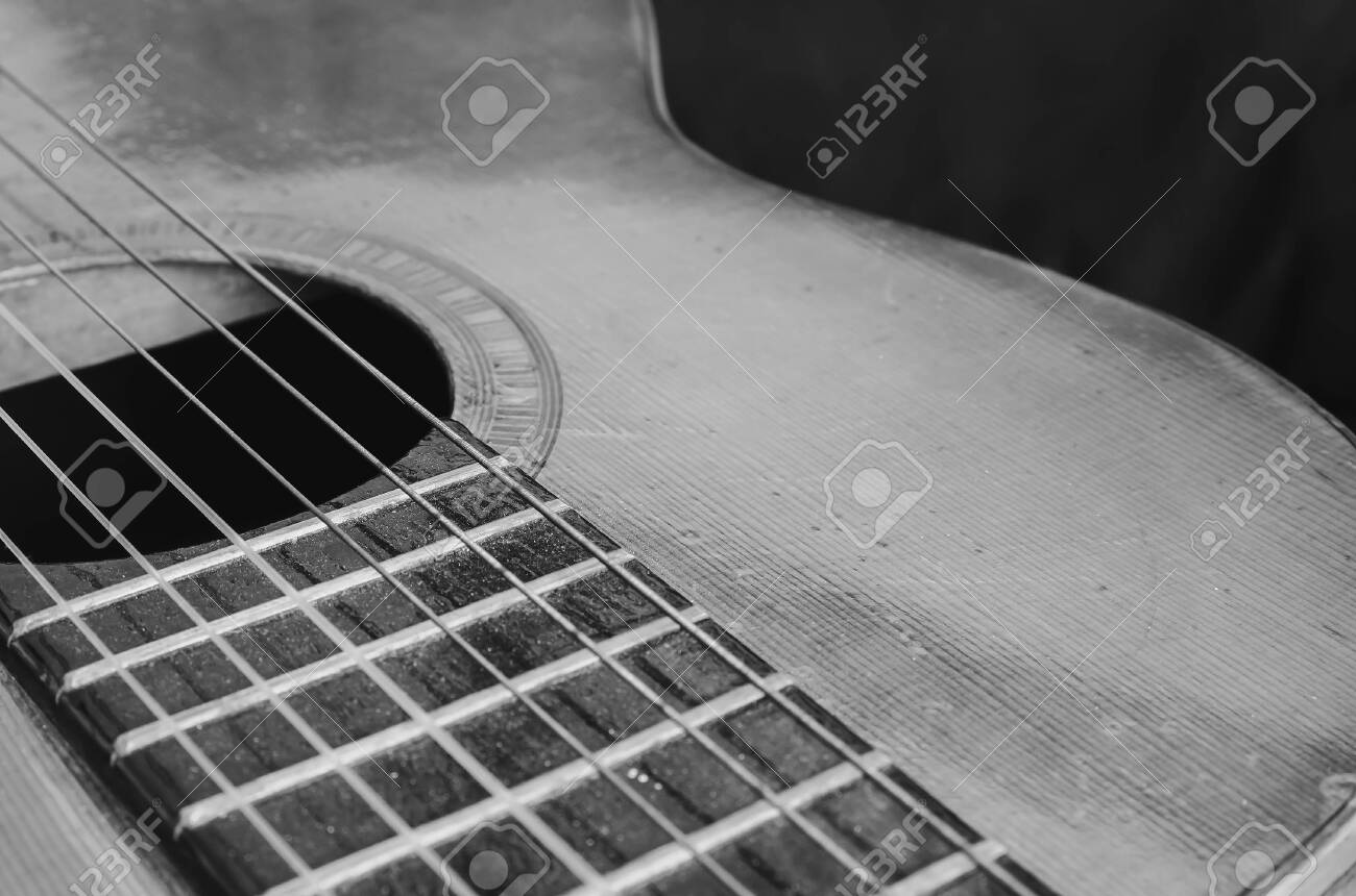 Details of an old acoustic guitar, the body curves, sound hole, frets and nylon strings. Wooden acoustic guitar, worn out and dusty. Black and white, macro photo, with depth of field. - 130103342