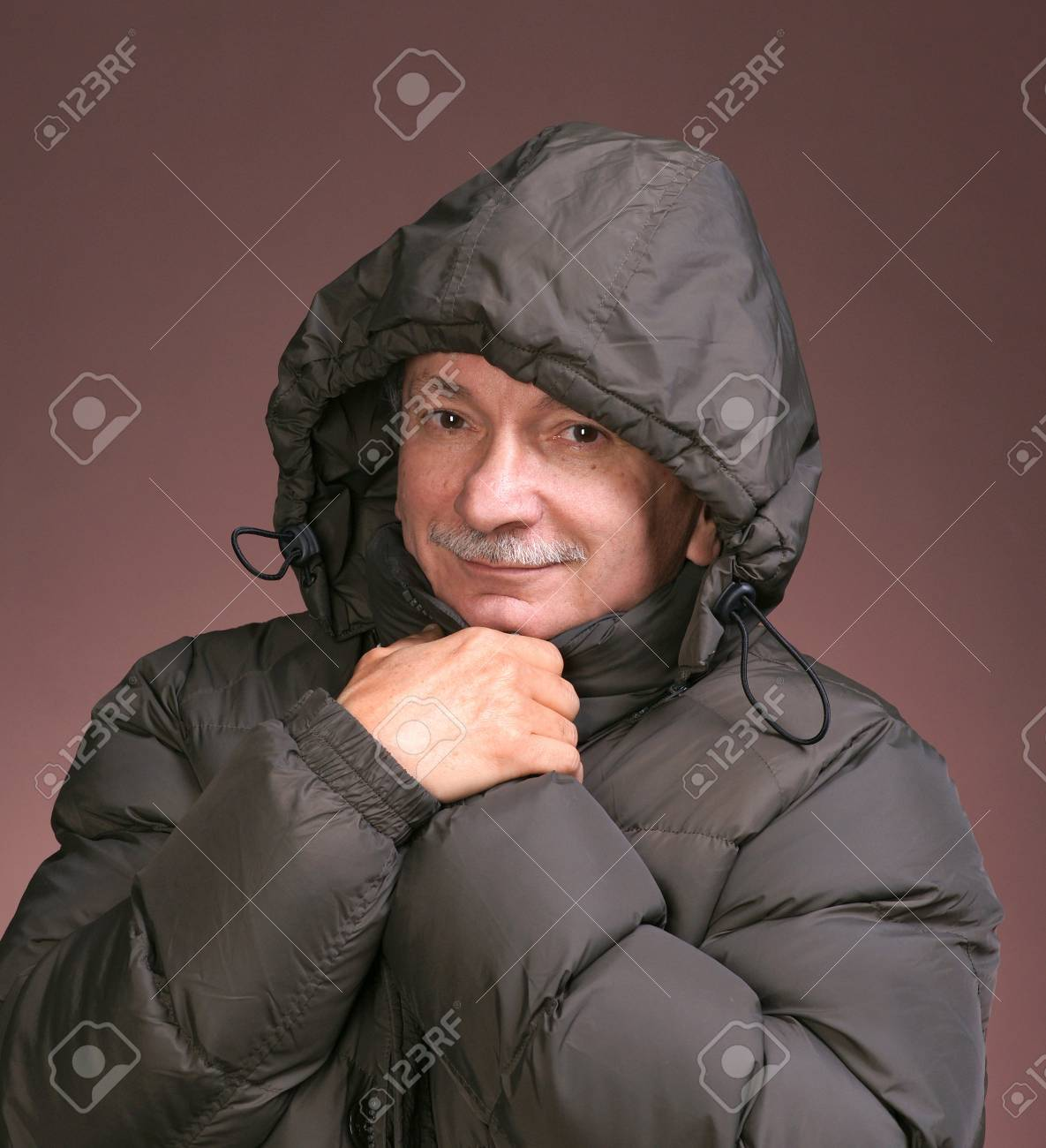 Close-up portrait of a senior man in winter clothing on a brown background Stock Photo - 17016955