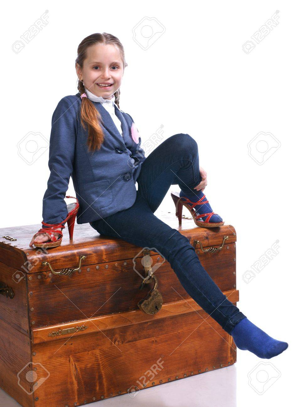 Beautiful girl sitting on a big box and trying on moms shoes Stock Photo - 17646429
