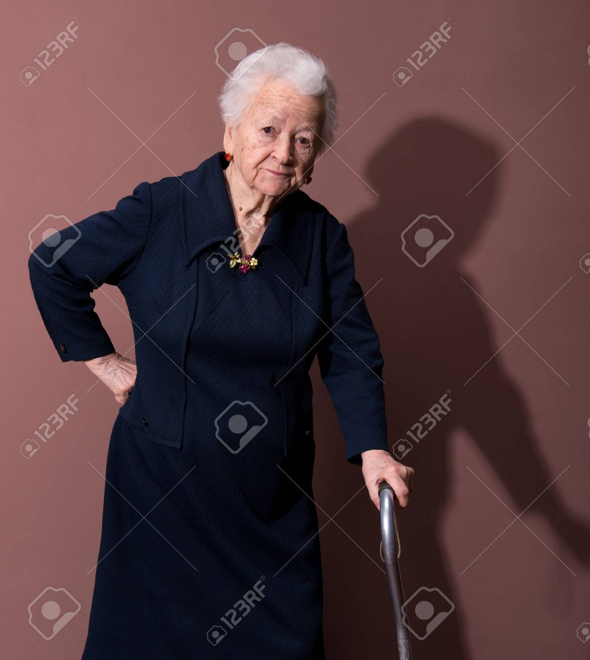 Old woman with a cane on brown background Stock Photo - 18442258