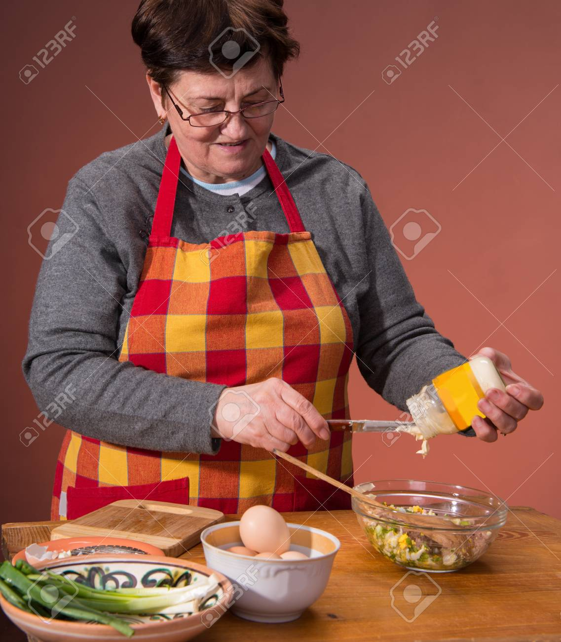 Woman preparing salad  on an orange background Stock Photo - 18434944