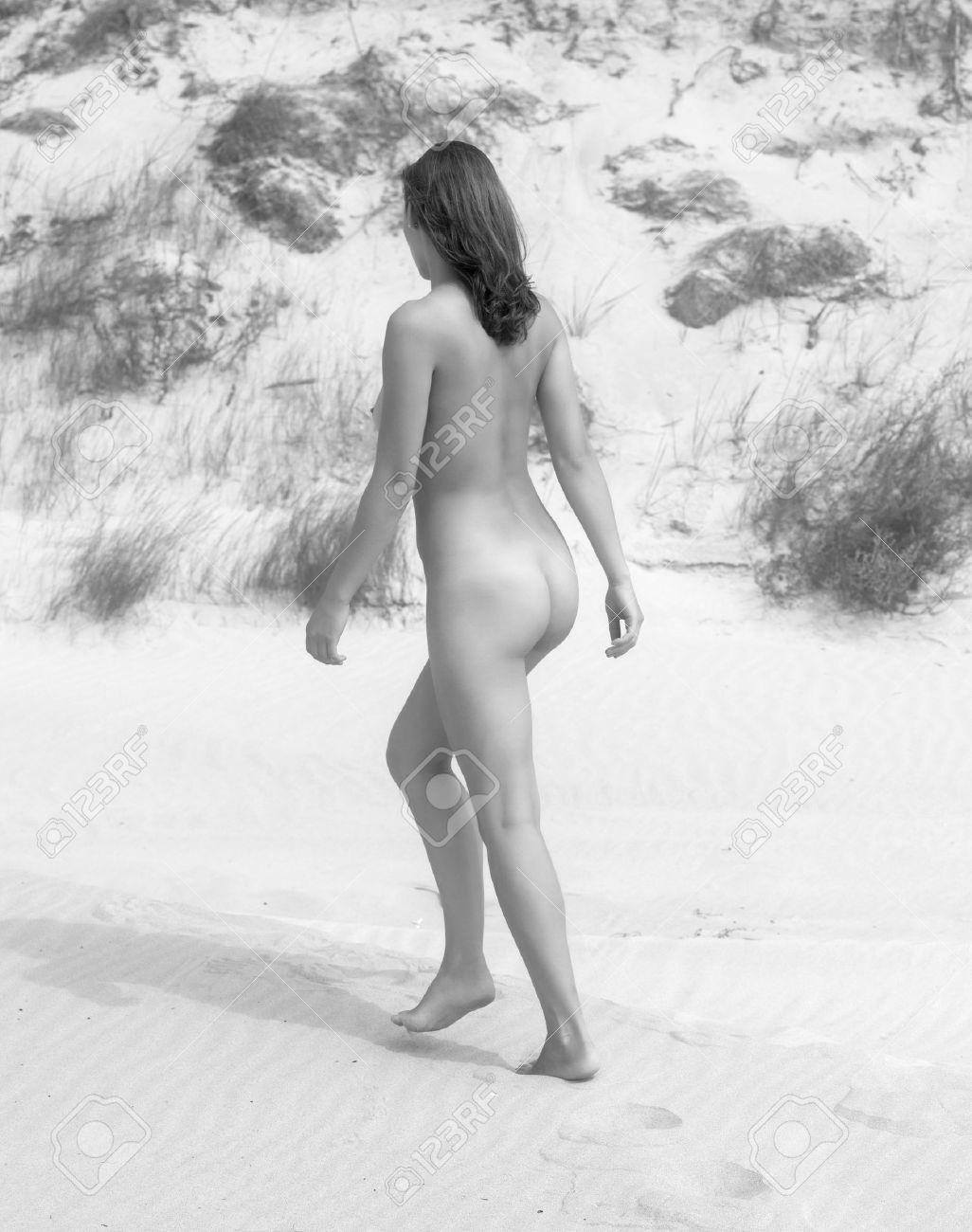 Nude black woman walking on beach