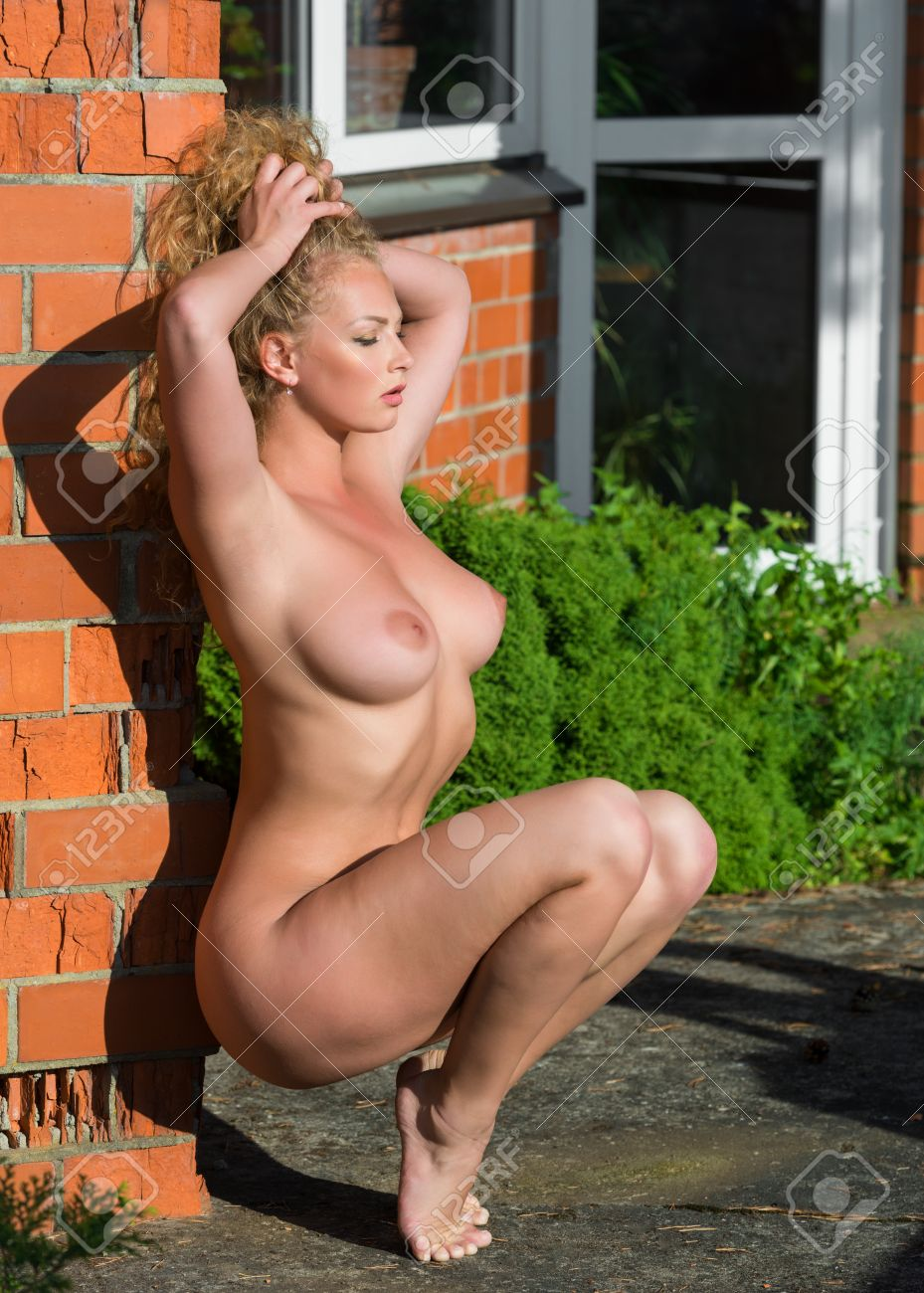 beautiful young naked woman posing near a brick wall stock photo