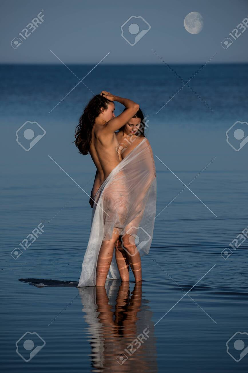Two young with white shawl posing on the beach in the evening. Sexy brunettes enjoying summer time outdoors - 133376946