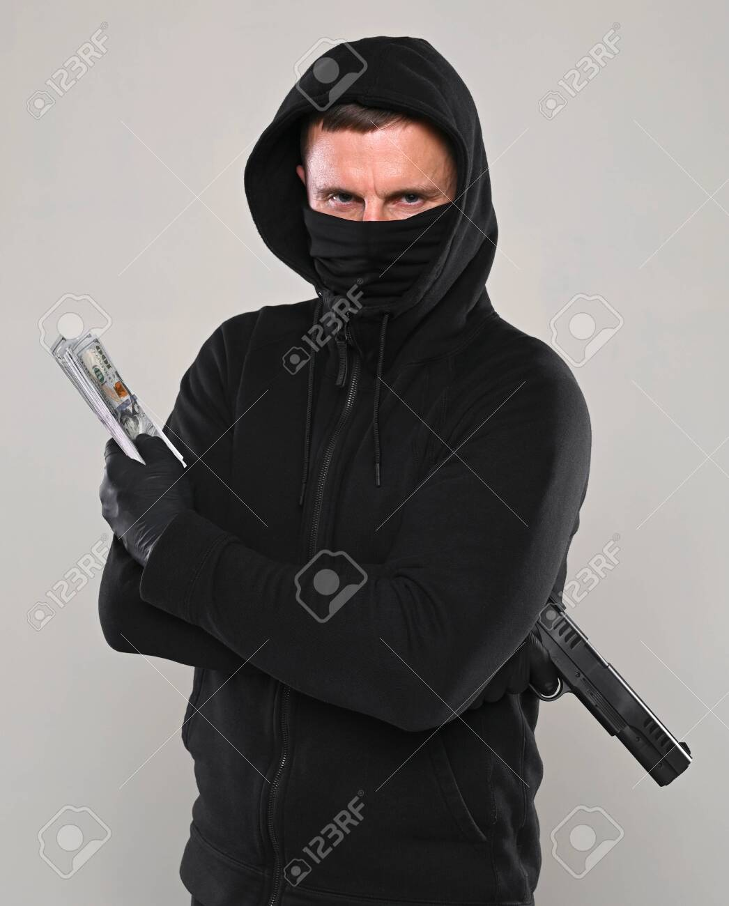 Man in black mask and hoody with a gun and pack of dollars over gray background - 143163093