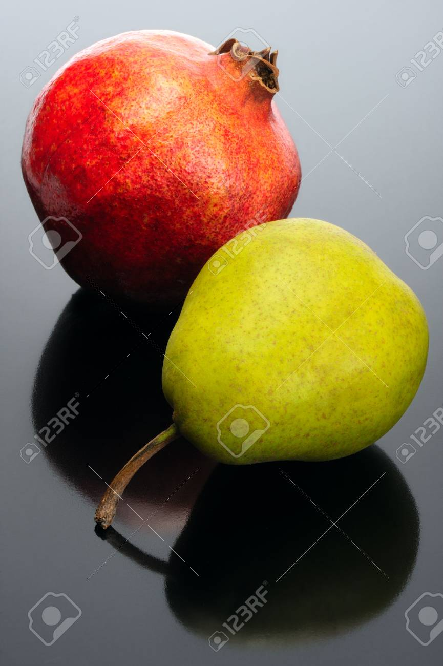 Pomegranate and pear on black background, with reflection. Stock Photo - 6437804