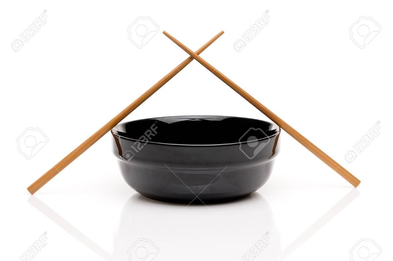 Crossed chopsticks on a black bowl on white Stock Photo - 7152672
