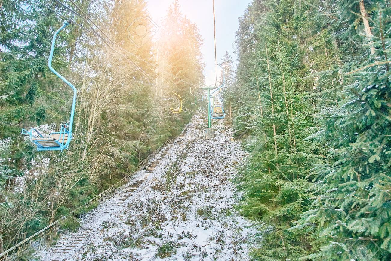 Ski Lift With Seats Going Over The Coniferous Forest And Mountain ...