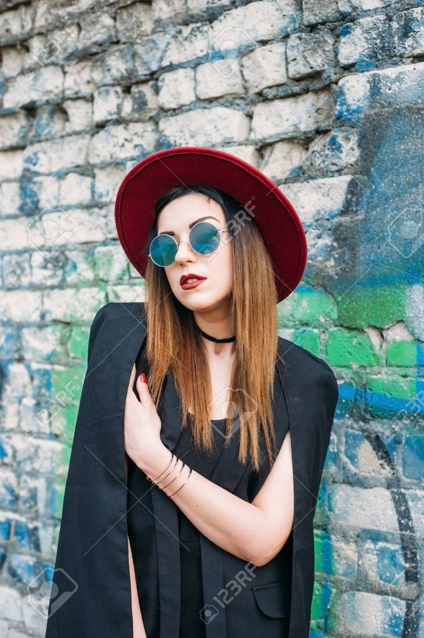 26967d91 Fashion pretty woman model wearing a red hat, green round sunglasses, black  jacket.