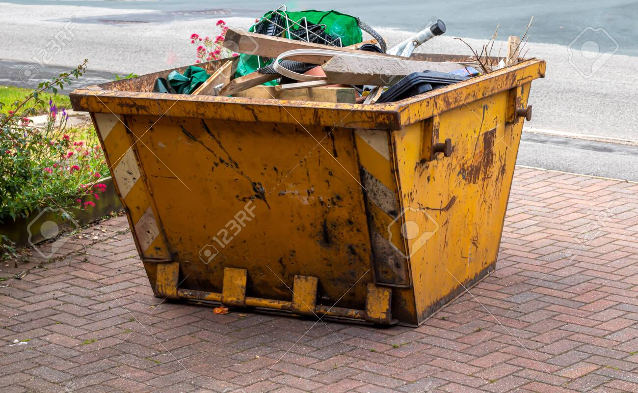 A yellow skip full of rubbish ready to be collection - 133613630