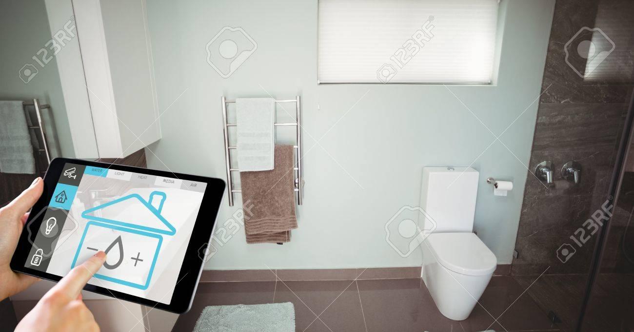 Digital composite of Hand using smart home application on digital tablet in washroom Stock Photo - 76884137