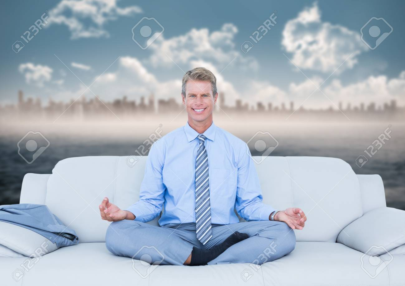 Digital Composite Of Business Man Meditating On Couch Against Water And  Blurry Skyline Stock Photo