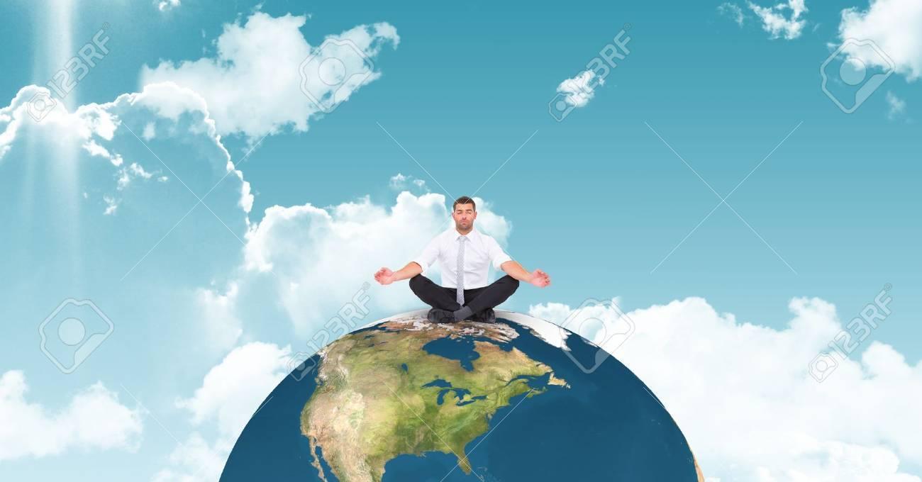 Digital composite of Businessman meditating on globe against sky Stock Photo - 79174657