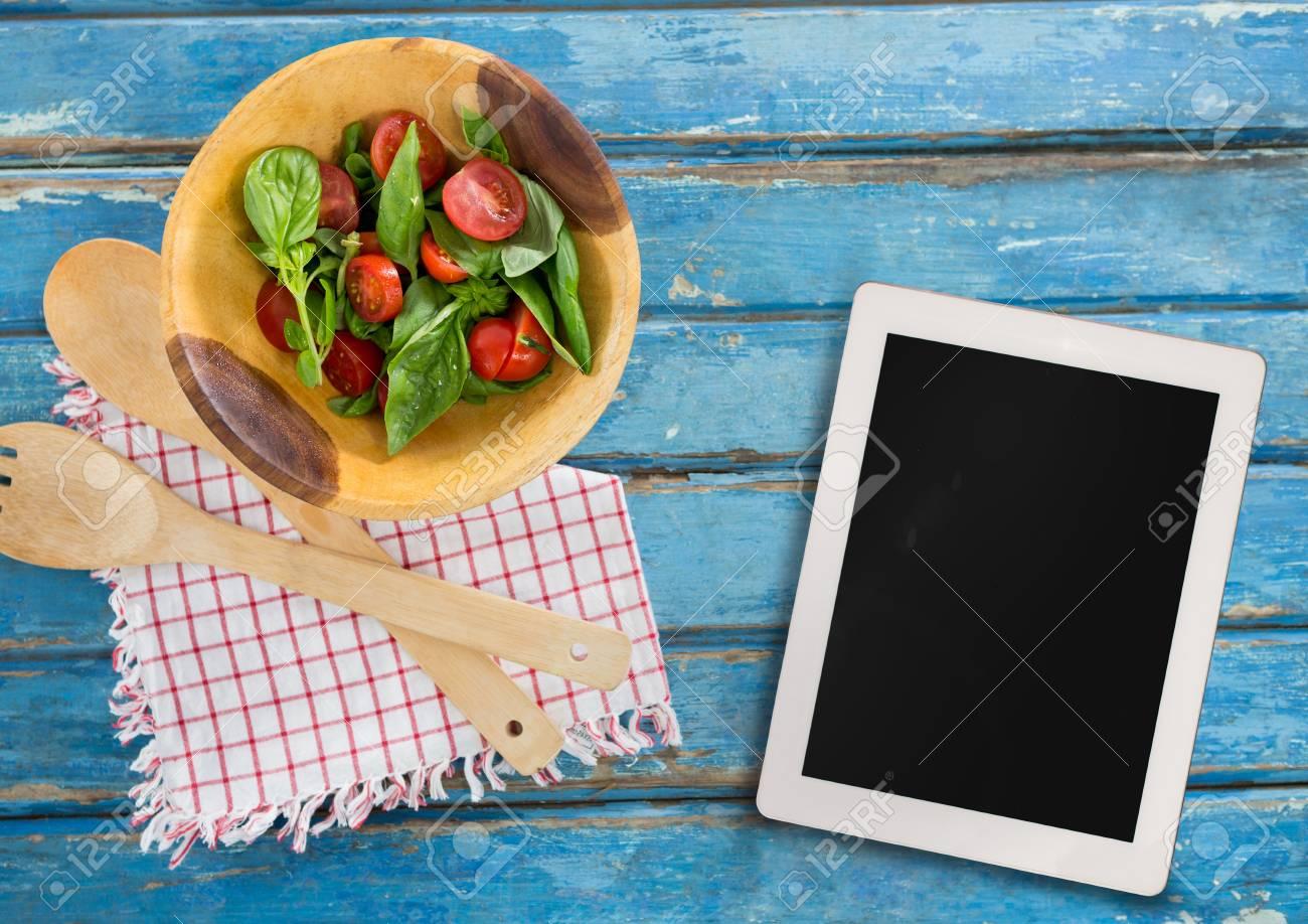 Composite numérique de tablette sur bureau en bois bleu avec de la