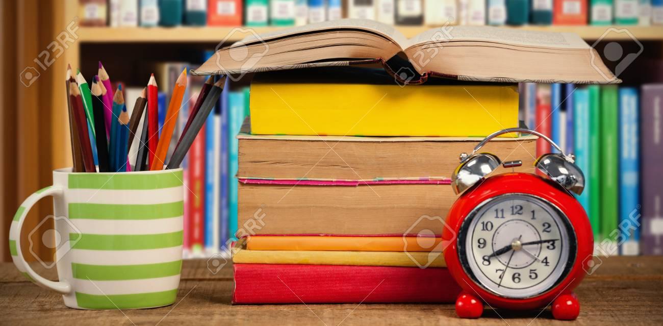 Pila De Libros Por Taza Con Lápices De Colores Y Despertador En La ...