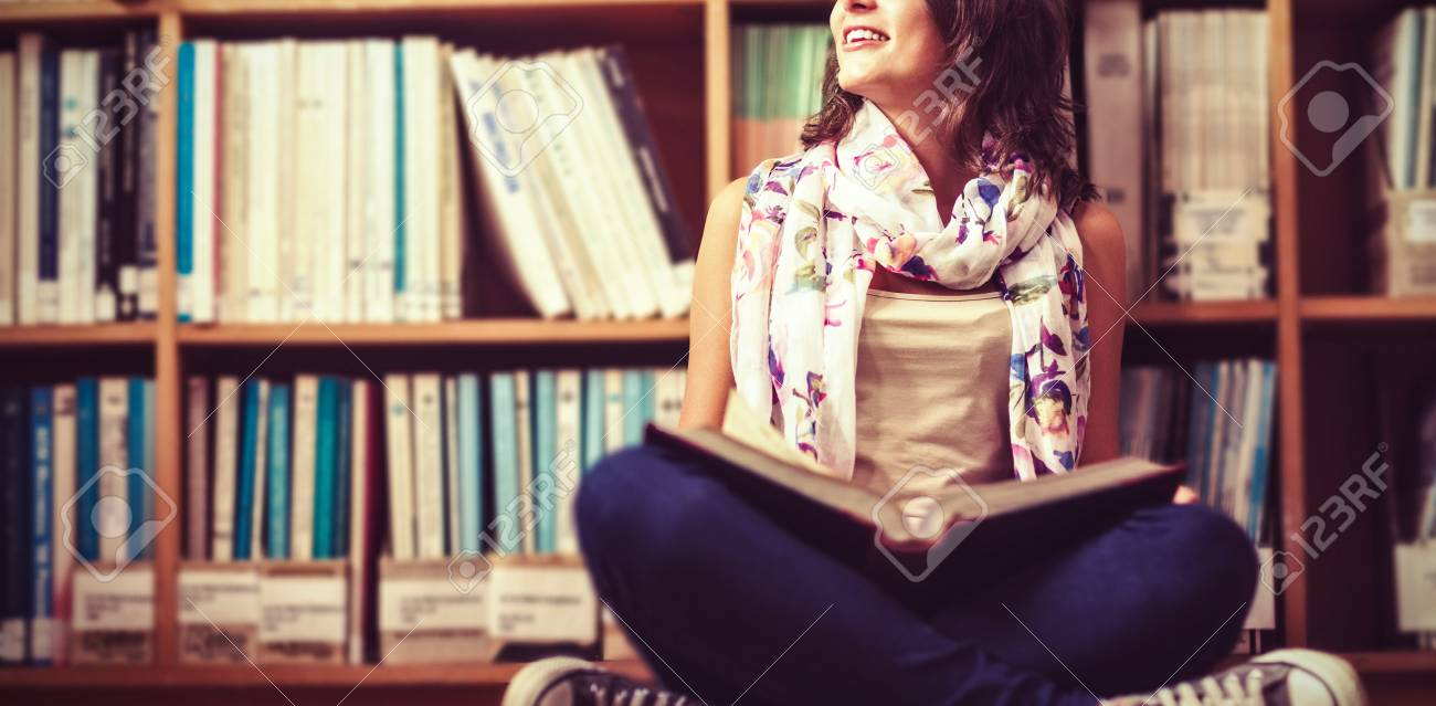 Thoughtful Female Student Sitting Against Bookshelf With Book