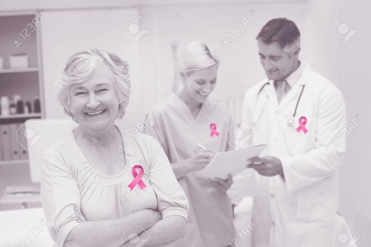 Breast cancer awareness ribbon against patient smiling while