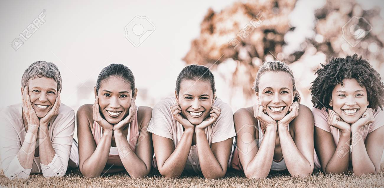 Portrait of smiling women lying in a row for cancer awarness in park - 85858207