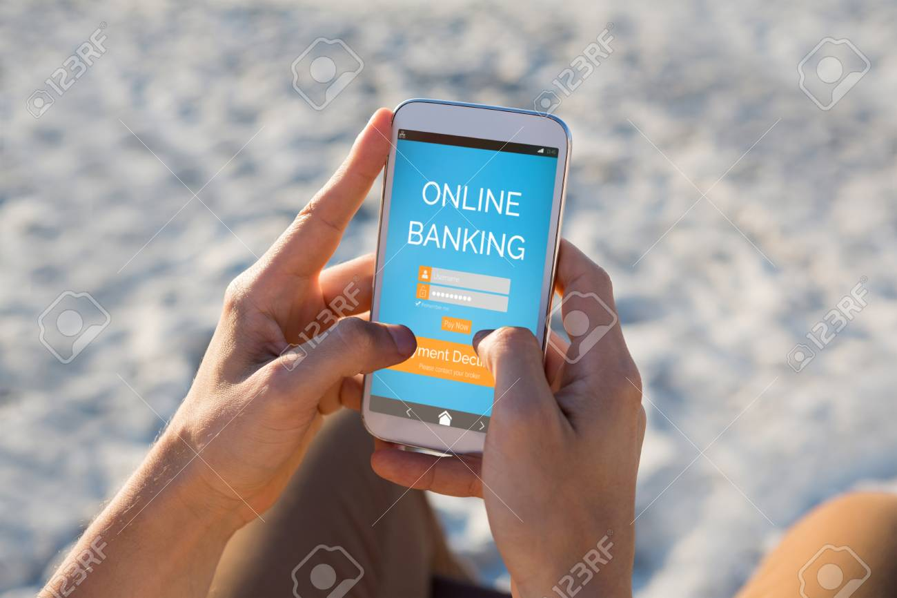 Online Banking Text On Blue Mobile Screen Against Hands Of Man Using