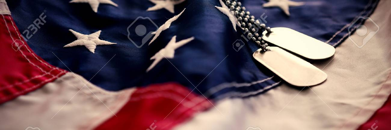 Dog tag chains on striped American flag - 87806436