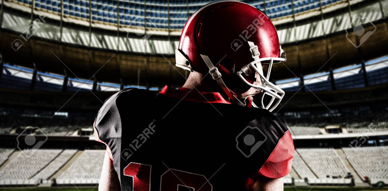 American football player in helmet looking off to the side against rugby goal post on a sunny day in the stadium - 129618770