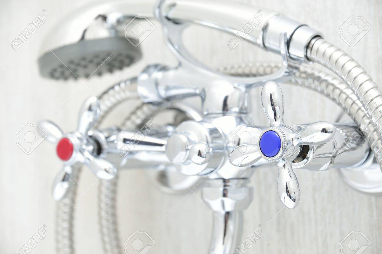 chrome faucet in bathroom with separate taps and showerhead - 37705649