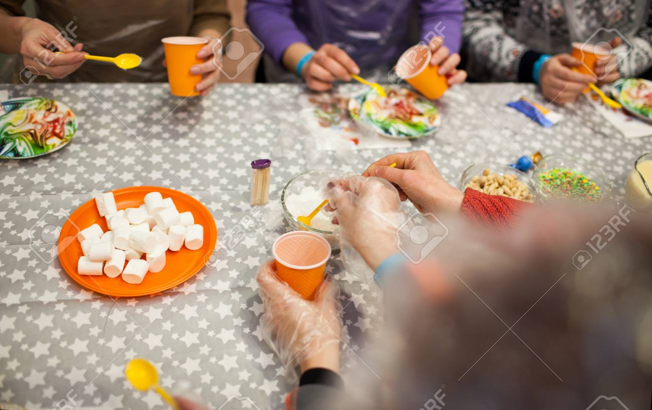 hands with spoons and plastic cups making sweets on colorful plates - 116150388