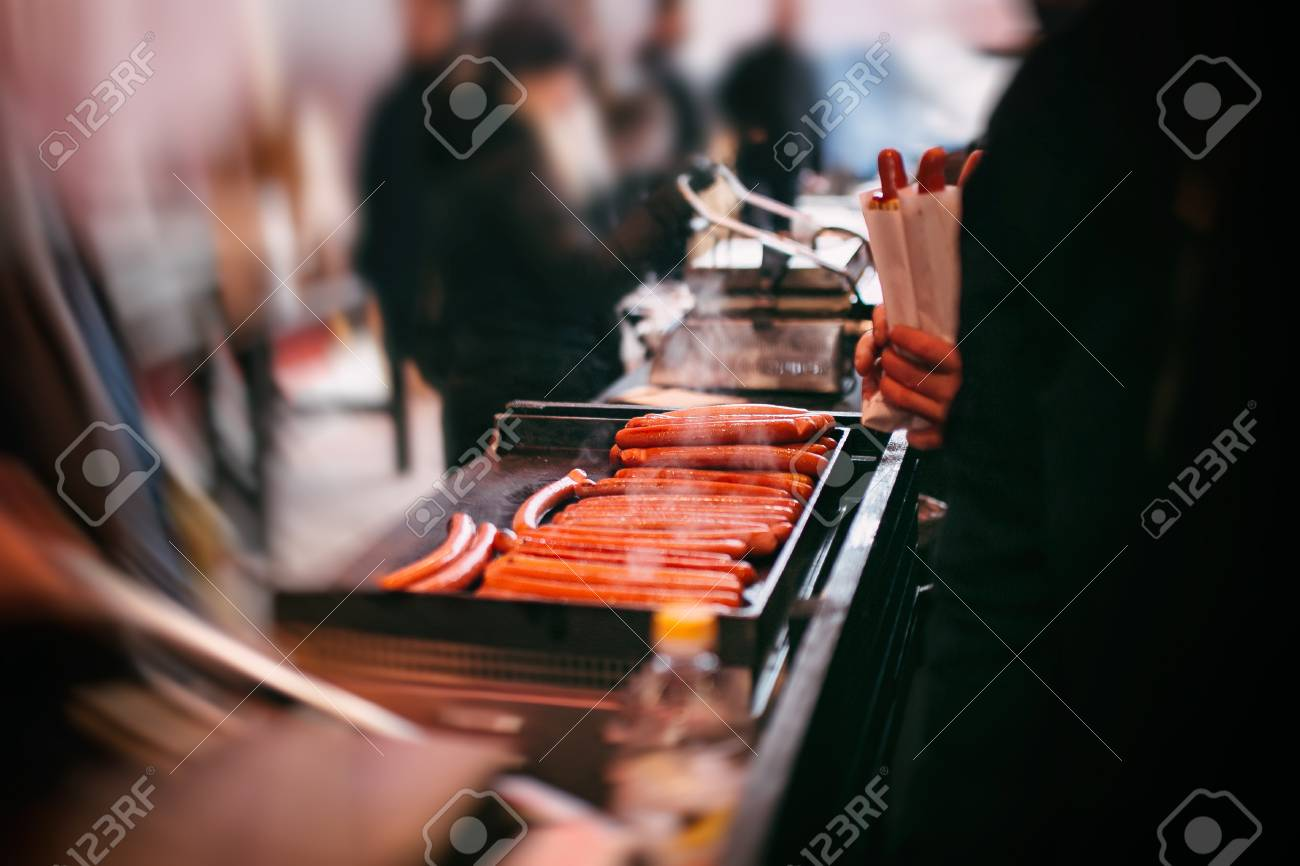 Cooking hot dogs on the street. sausage cooking for hot dog. electric stove for sausage roasting. commercial equipment for cafe and street food. - 116150392