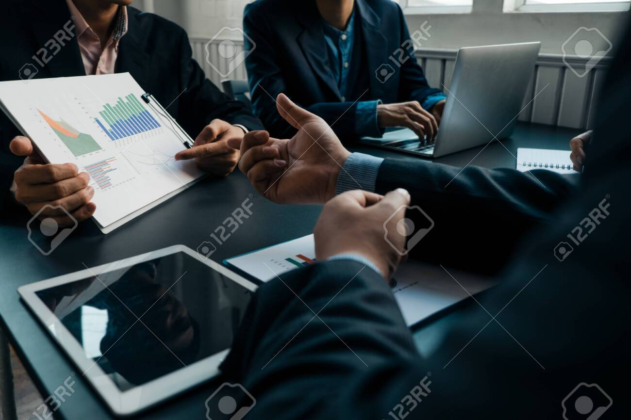 Businesspeople analyzing investment graph meeting brainstorming and discussing plan in meeting room, investment concept - 124369649