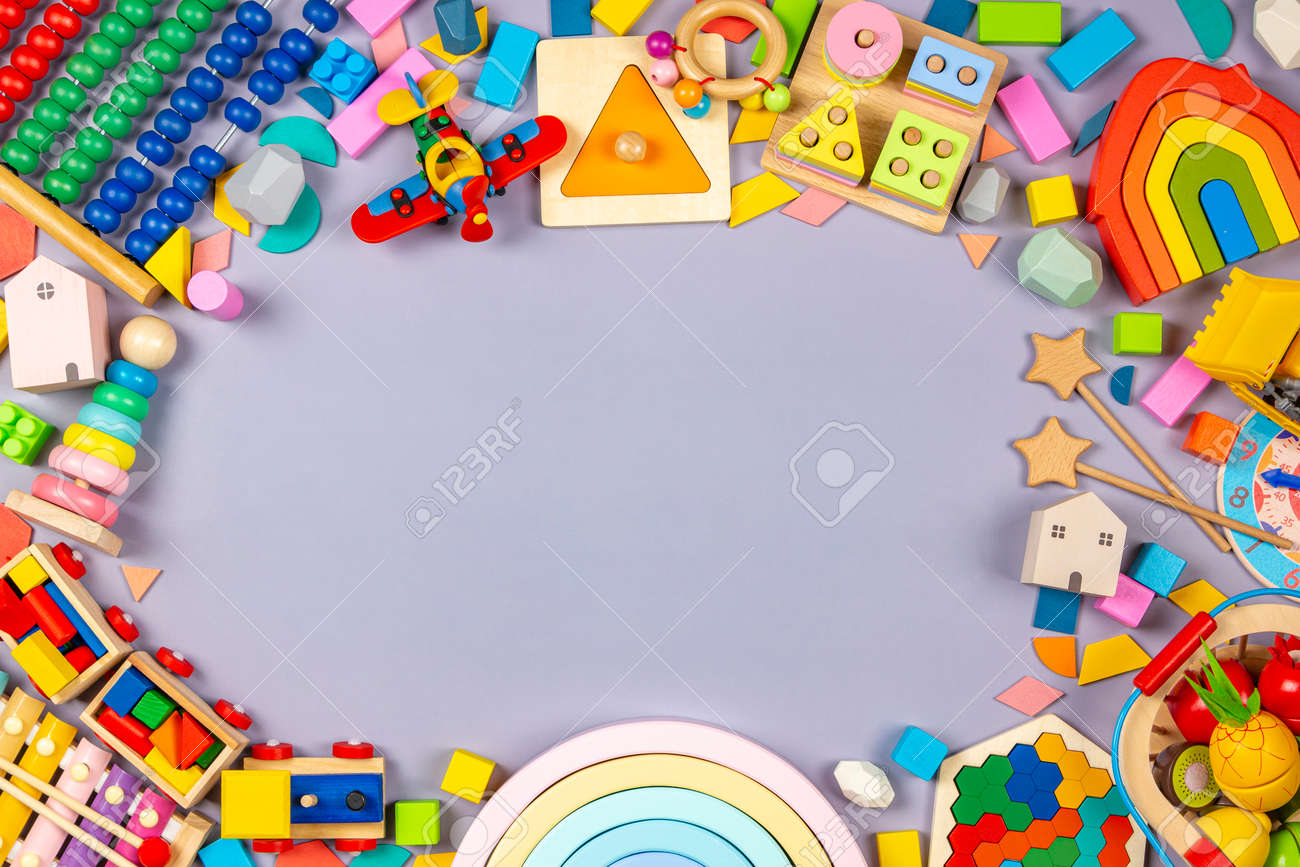 Baby kids toys frame. Colorful educational wooden plastic and fluffy toys for children on gray background. Top view, flat lay - 168153904