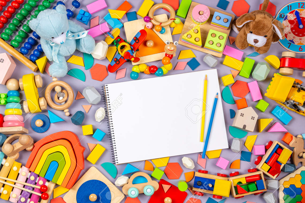 Colorful educational wooden plastic and fluffy baby kids toys and blank notebook with colored pencils on gray background. Top view - 169897464