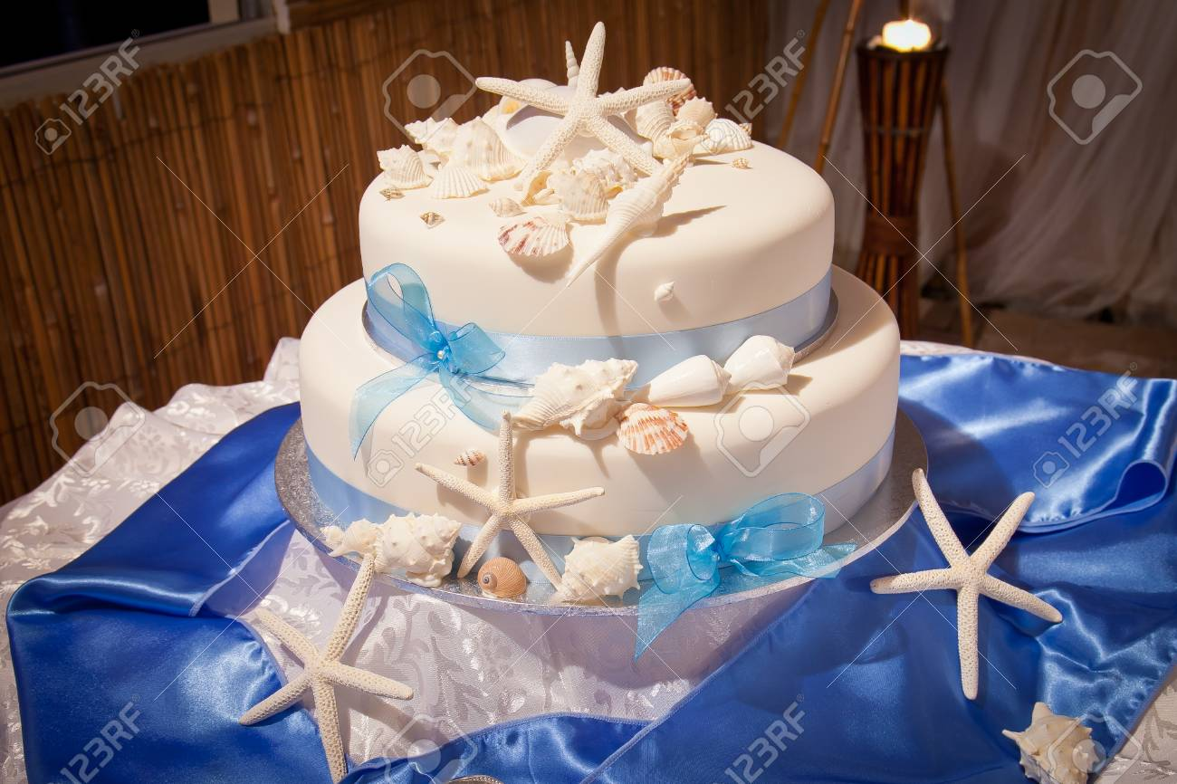 Beach Theme Wedding Cake With Starfish Shells And Blue Ribbon Stock