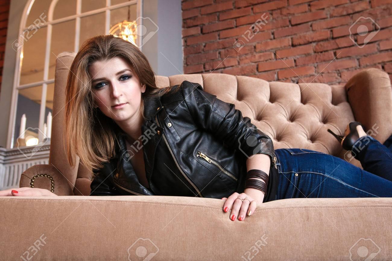 big sale 56571 7bf08 Ragazza affascinante in giacca di pelle con le pompe alto che si trova su  un sofà