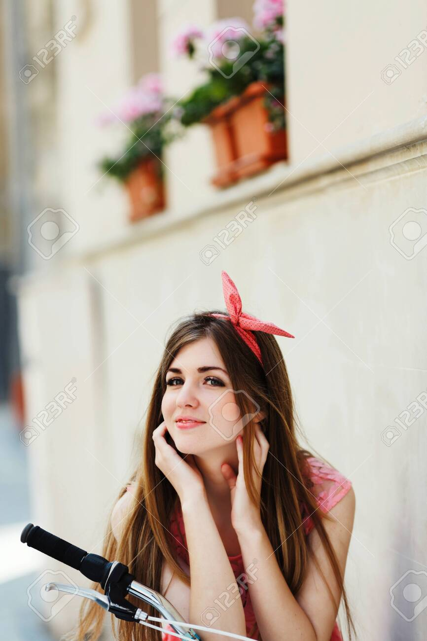 sensitive girl, looking at camera, sitting on a bicycle - 122488697