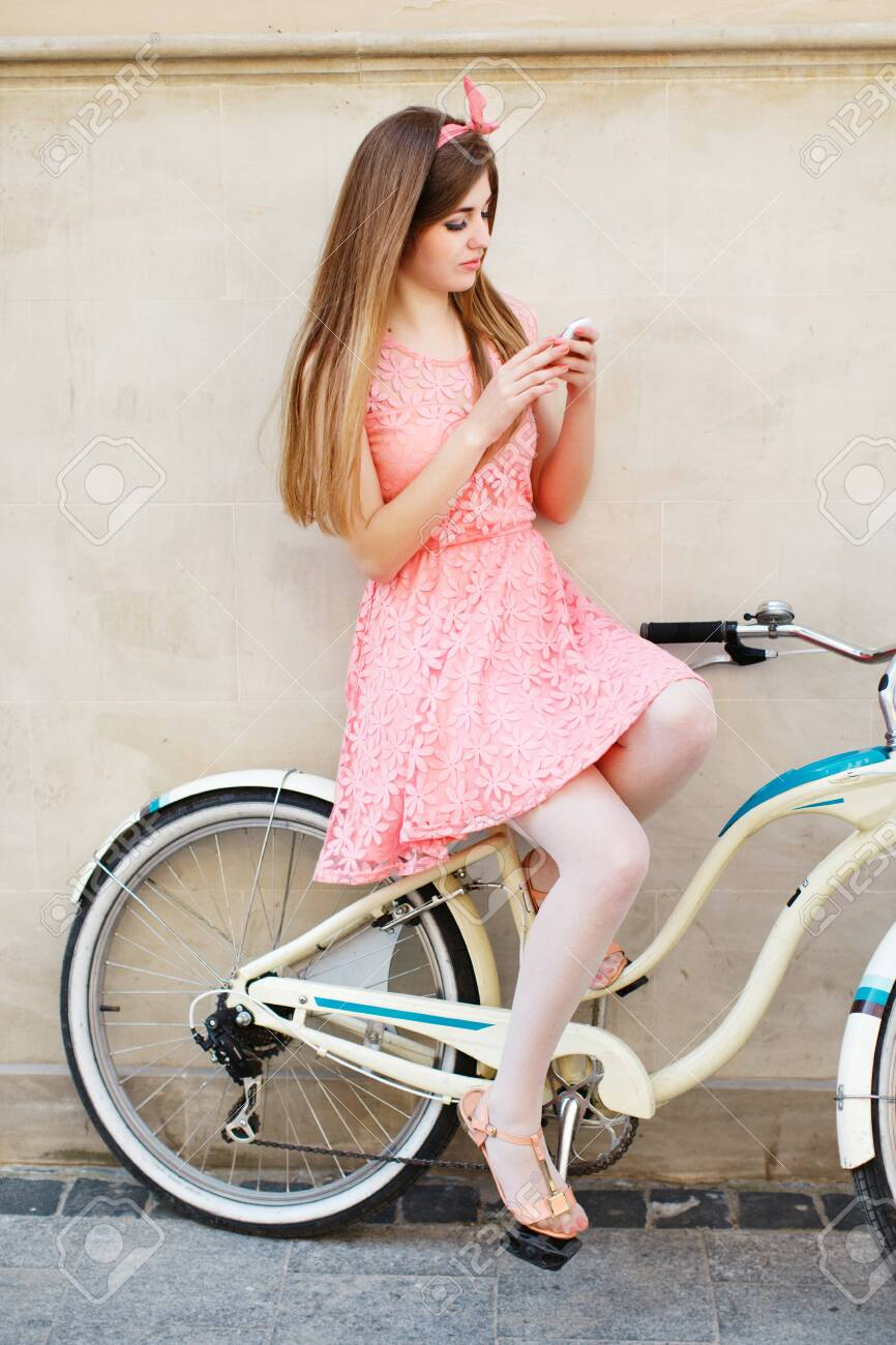 girl sitting on vintage bicycle and using smartphone - 122488712