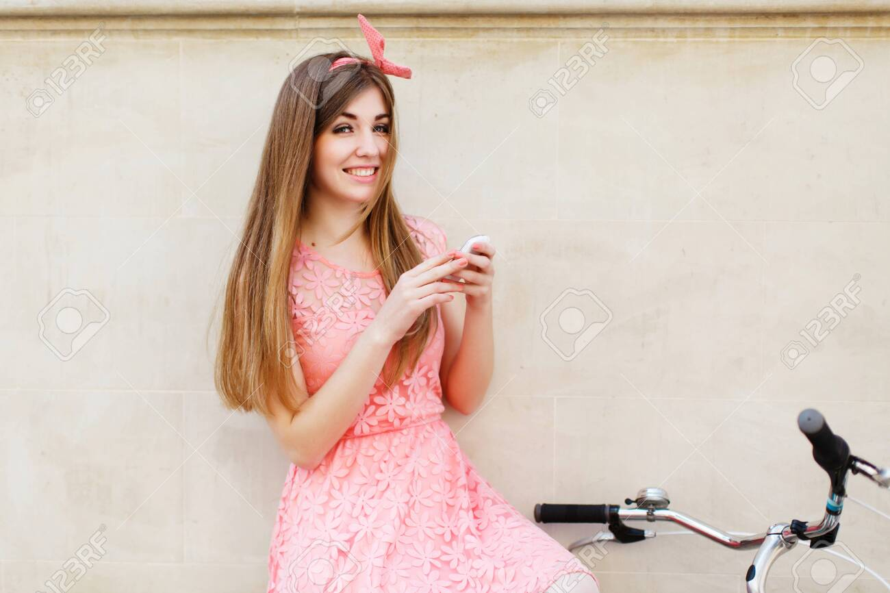 girl smiling and holding smartphone - 122491595