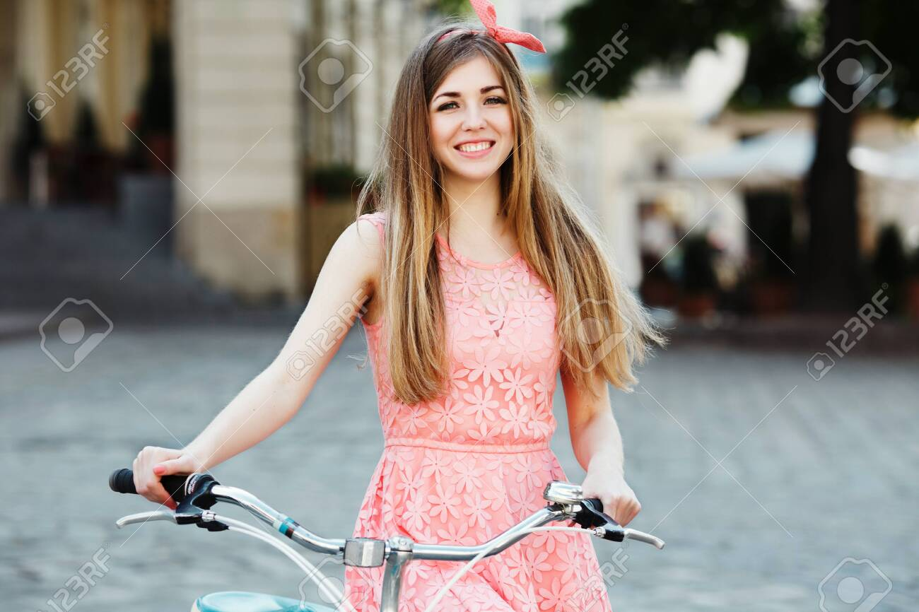 blond-brown girl smiling and holding bicycle. - 122488716
